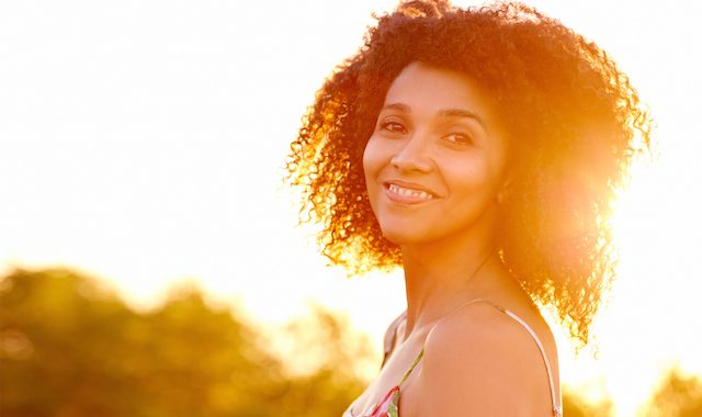 Closeup Of A Beautiful Young Woman With A Sunset Behind Her